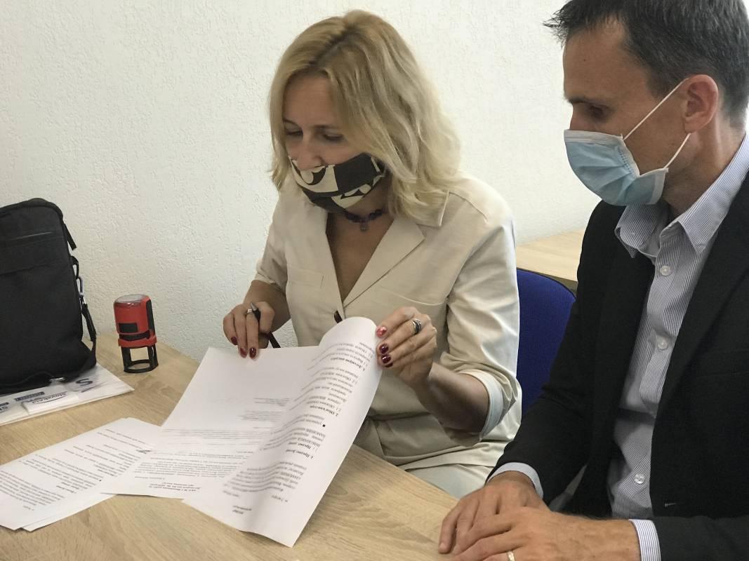 Галина Шумицька та Павло Паніс підписують документи