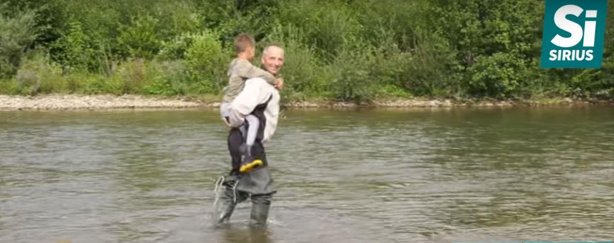 Батько несе дитину через річку - Тячівщина